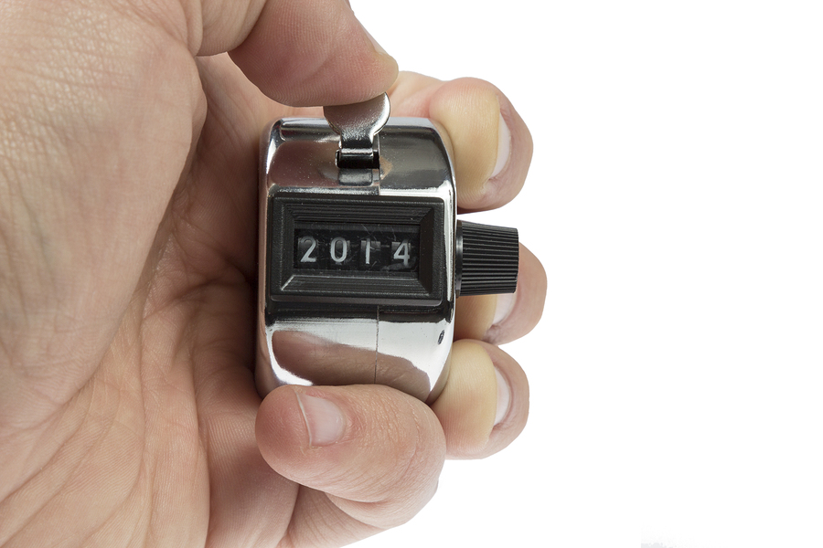 Hand held tally counter showing 2014 holded by male hand isolated on white background