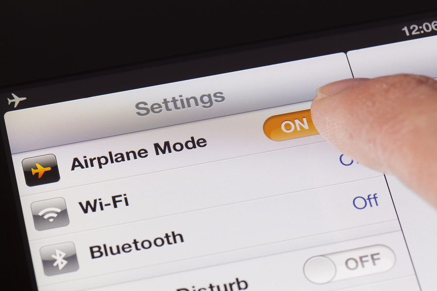 Adelaide, Australia - October 3, 2012: Switching to Airplane mode on an iPad. Airplane mode is a setting on iPhone and ipad that. when switched on, will disable the device's capacity to place or receive calls or text messages.